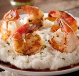 Perfectly creamy and extra cheesy grits topped with grilled shrimp and bourbon sauce for the perfect southern comfort food.